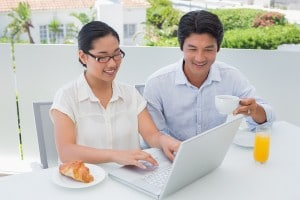 Smiling couple having breakfast together using laptop outside on a balcony